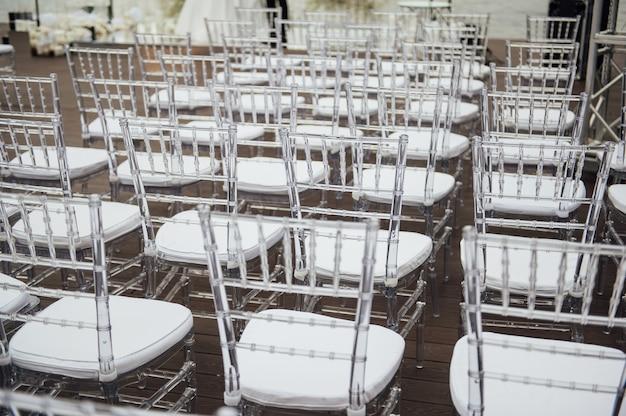 美しい結婚式の外出式でガラスの椅子が一列に並んでいます