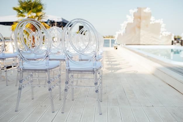 유리 의자는 아름다운 결혼식 나들이 행사에 나란히 서 있습니다.