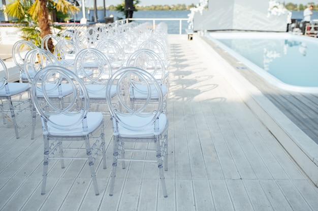 Glass chairs stand in a row in a beautiful wedding outing ceremony.