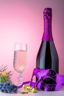 Glass of champagne, bottle, carnival mask and ornaments on pink background