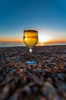 A glass of champagne on the coast stands on the sand against the sunset