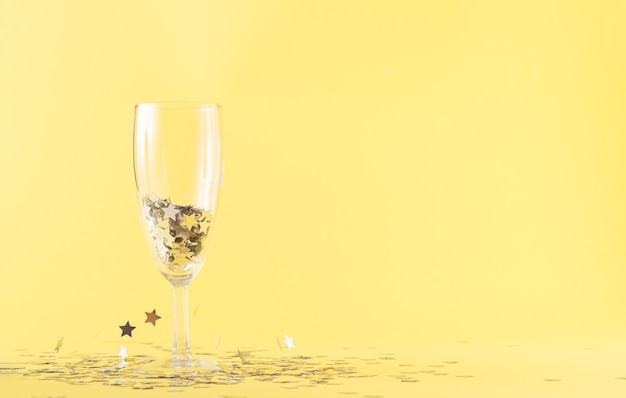 A glass of champagne filled with gray stars on a yellow background. gray stars hover in the air around the case. party and celebration concept with large copy space