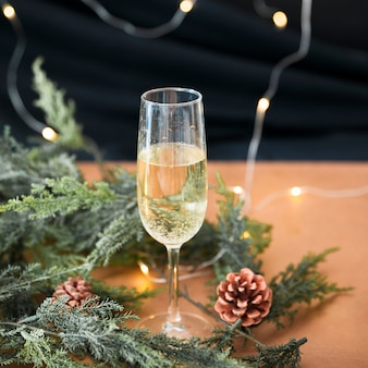 Glass of champagne with green branches
