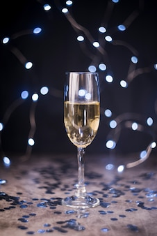 Glass of champagne with party decoration at night