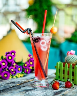 A glass of cherry cocktail with ice and plastic straw pipes