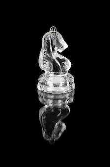 Glass chess knight on black isolated background.