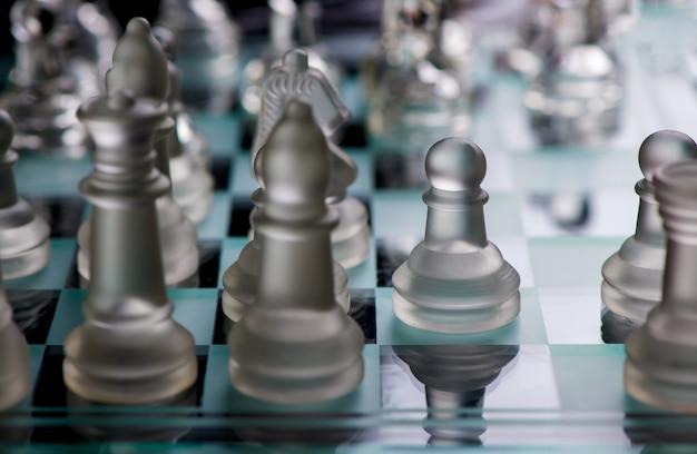 Стеклянные шахматные фигуры защищают короля на борту в темноте