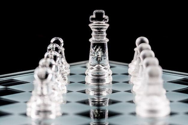 Glass chess pieces on a glass chessboard with reflection.