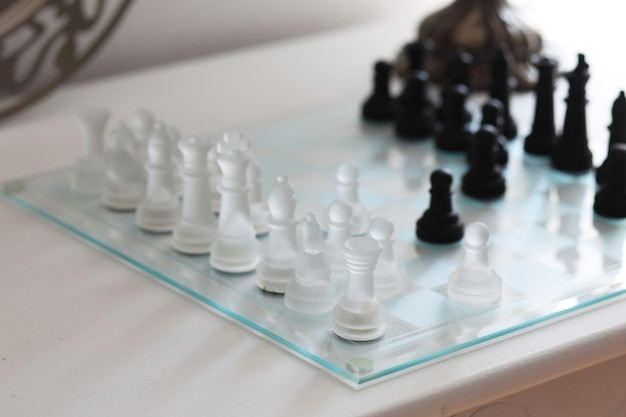 Glass chessboard with black and white chess figures on white surface.