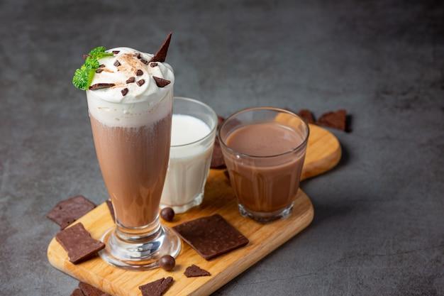 Glass of chocolate milk on the dark surface.