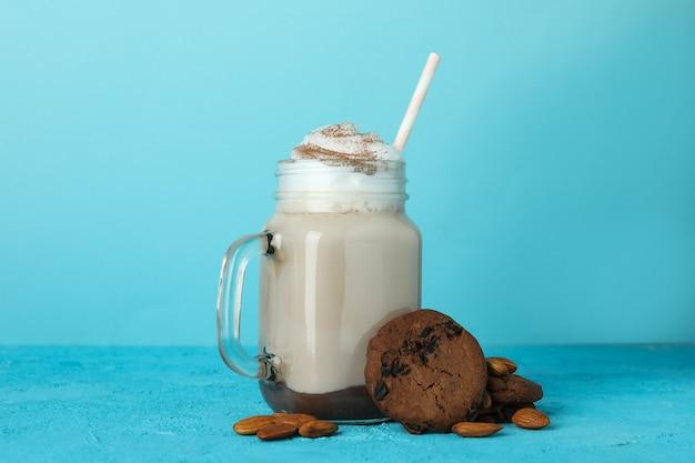 Glass of chocolate milkshake, cookies and almond on blue wall