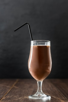 Glass of chocolate milkshake with straw and copy space