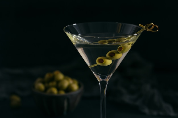 Glass of classic dry martini cocktail with olives on dark stone table against a black background.