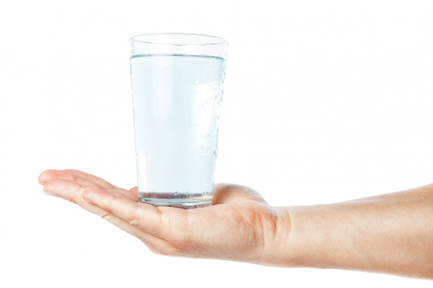 A glass of clean and fresh water in the hand of man. on a white wall.