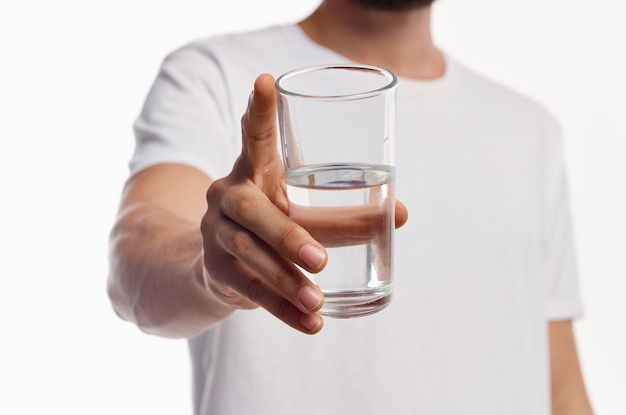 A glass of clean water in the hand of a man in a light shirt cropped view.