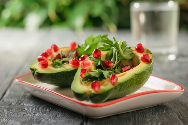 A glass of clean water with avocado halves filled with pomegranate seeds and parsley on a wooden table. vegetarian cuisine for weight loss.