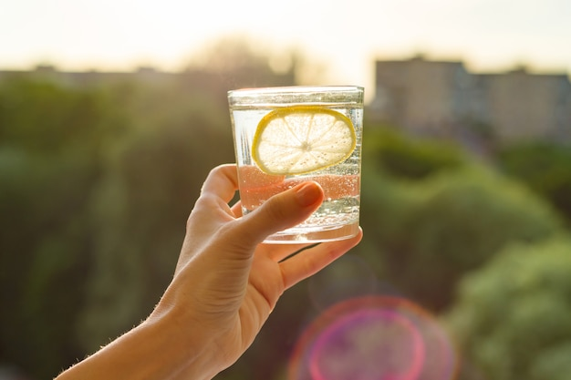 Glass of clear, sparkling water with lemon in hand
