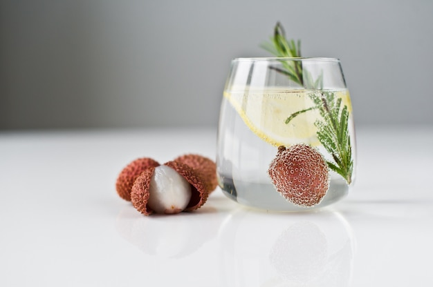 Glass of clear water with lemon, rosemary, lychee.