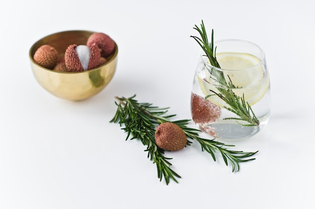 Glass of clear water with lemon, rosemary.