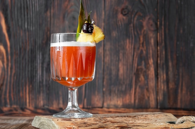 Glass of club cocktail garnished with pineapple wedge and maraschino cherry