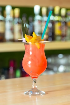 Glass of cocktail decorated with fruits at bar counter.