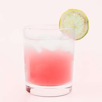 Glass of cocktail drink with an lemon slice against pink background