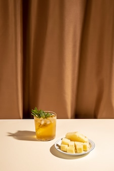 Glass of cocktail drink with pineapple slices on plate over white table against brown curtain