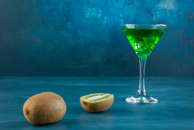 Glass of cocktail and fresh kiwi fruits on blue surface.