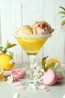 Glass of cocktail, ingredients and flowers against wooden background