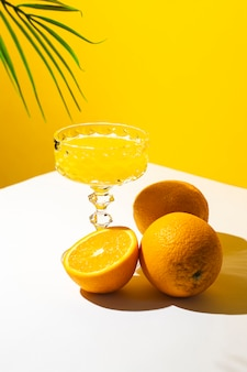 Glass of cocktail or orange juice under the shade of a palm tree and sunlight.