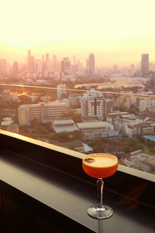 Glass of cocktail on the rooftop bar with aerial urban view in background.