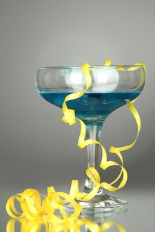 Glass of cocktail and streamer after party on gray background