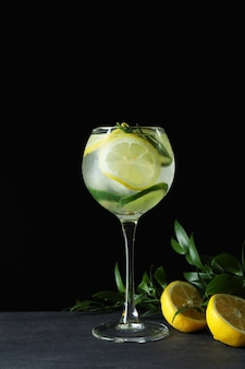 Glass of cocktail with citrus on dark