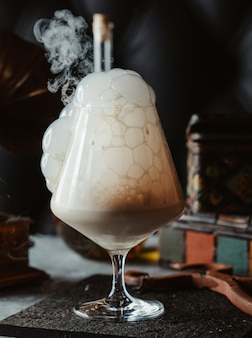 A glass of cocktail with cream bubbles
