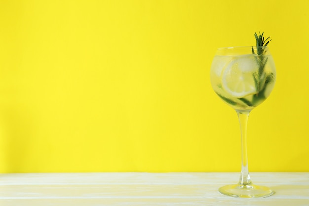 Glass of cocktail with lemon and rosemary on yellow