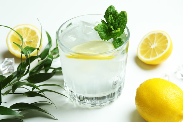 Glass of cocktail with lemon on white