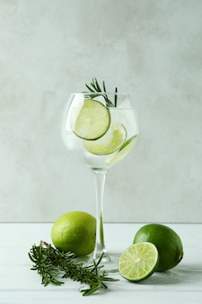 Glass of cocktail with lime on white wooden table