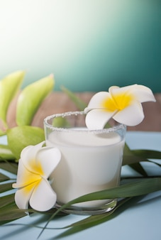 Glass of coconut milk with flowers plumeria and palm leaf