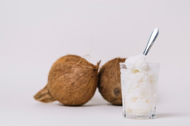 Glass of coconut oil with coconut nuts