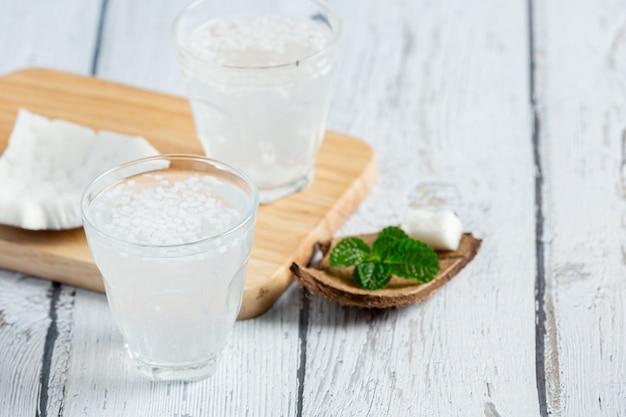 Bicchiere di acqua di cocco messo su fondo di legno bianco