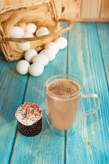 Стеклянная кофейная чашка. пасхальный кулич и яйца в корзине на сене. деревянный бирюзовый стол.