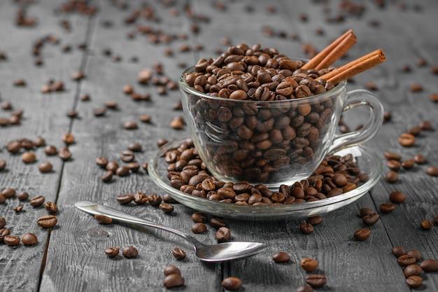 ガラスのコーヒーカップとコーヒー豆と黒の木製のテーブルに金属のスプーン。