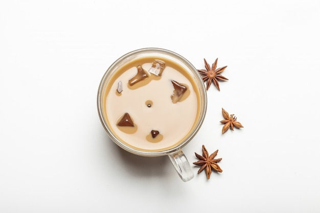 Glass of coffee with cinnamon stars isolated on white