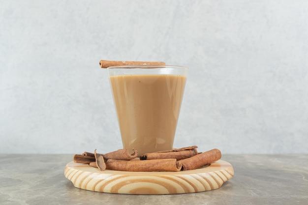 Bicchiere di caffè con cinnamons su tavola di legno.