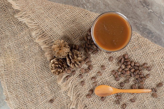 Bicchiere di caffè con chicchi di caffè e cucchiaio su tela