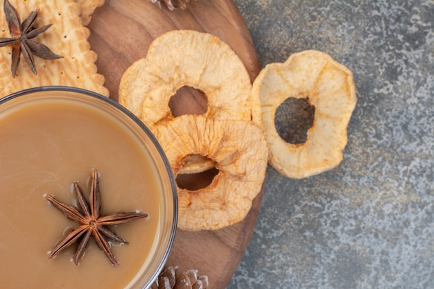Glass of coffee with dried apple rings and biscuits on wooden board.