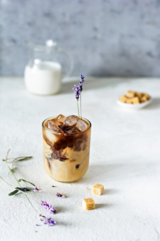 A glass of coffee with ice, milk (cream) and lavender flowers