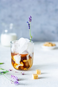 Glass of coffee with ice, milk and lavender flowers on a light background