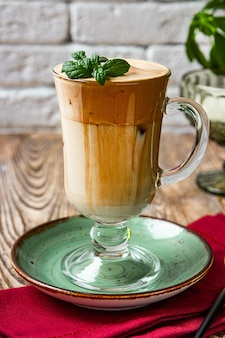 A glass of coffee with milk decorated with mint leaves, dalgon coffee.