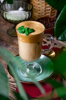 A glass of coffee with milk decorated with mint leaves on the table in a cafe, dalgona coffee, vertical photo.